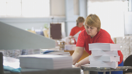 Female worker disassembles a stack of paper in the typography