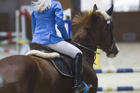 Rear view of female equestrian on the ginger stallion at show jumping competition