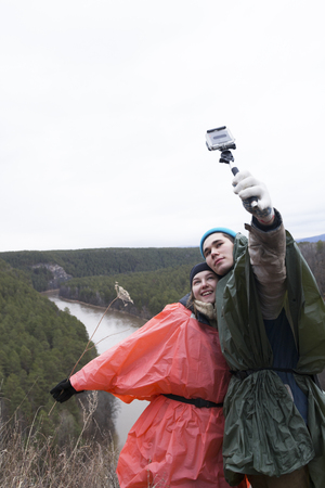 Young loving couple making selfie in the hillside to the river