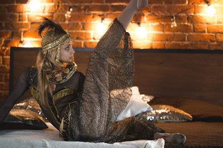 gimnasta de circo hermosa que presenta la danza con una serpiente en la cama