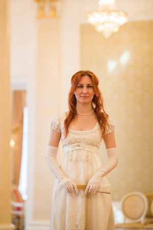 Pretty red haired woman in vintage 18 centuries dresses use fan in luxury ballroom