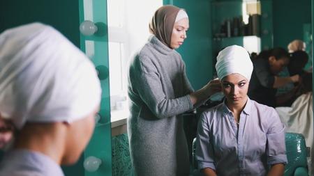 Muslim woman preparing islamic wedding headdress for the beautiful bride Imagens
