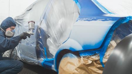 Professional car man painter in vehicle workshop