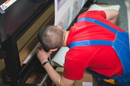 Male worker in typography inserts the paper in the printing press Banco de Imagens