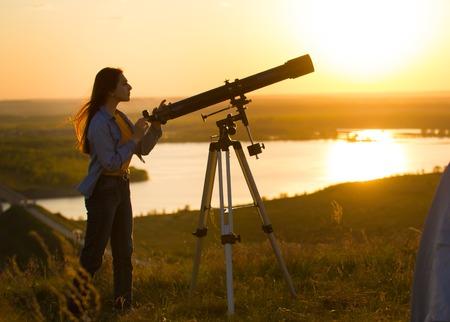 Silueta de mujer joven mirando a través del telescopio al atardecer de verano
