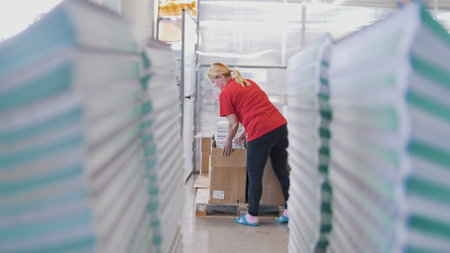 Female worker puts printed magazines in a box through the paper stacks Banque d'images