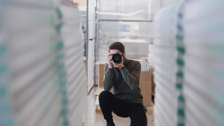 Young male professional photographer shooting in front of paper stacks in the typography