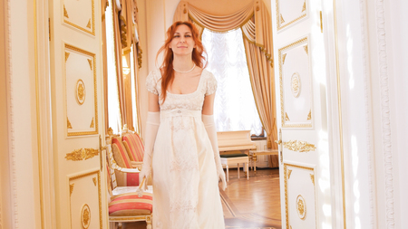 Beautiful woman in a ball gown walks into the ballroom
