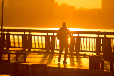 Male silhouette engaged in sports walking on the promenade at bright sunset
