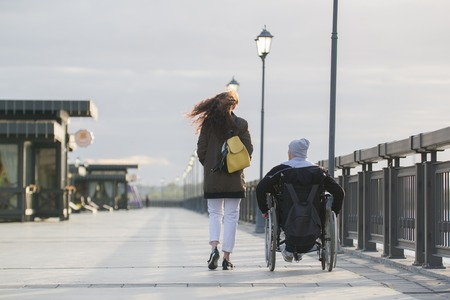 Rear view of young woman walking with disabled man in wheelchair on the quay Stock Photo