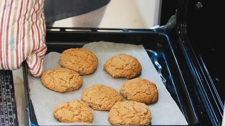 Hand in the mitten pulls out of the oven homemade cookies