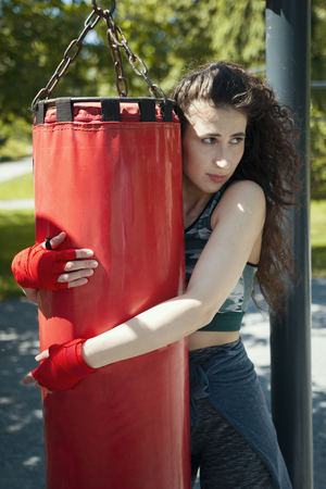 Portrait of young woman in sportswear hugging the punching bag Reklamní fotografie