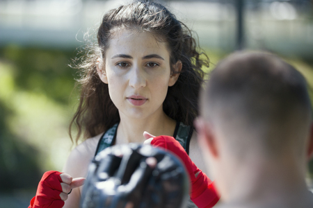 Portrait of young woman in sportswear at boxing workout in summer park