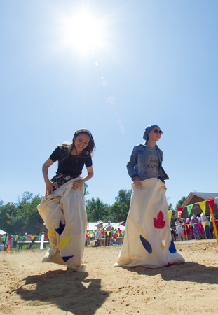 KAZAN, RUSSIA - JUNE 23, 2018: Traditional Tatar festival Sabantuy - Young women having fun playing traditional game, jumps in bags under the sun
