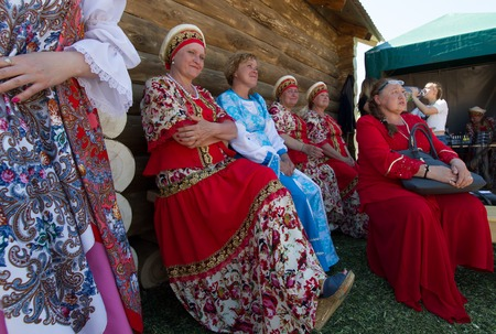 KAZAN, RUSSIA - JUNE 23, 2018: Traditional Tatar festival Sabantuy - Mature women artists in russian national dresses sitting on the bench