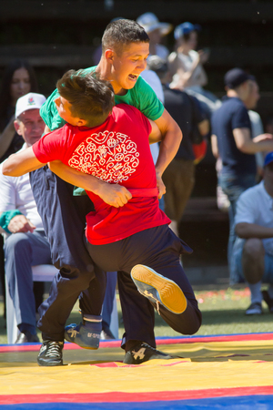 KAZAN, RUSSIA - JUNE 23, 2018: Traditional Tatar festival Sabantuy - Two male teenagers fighting in folk wrestling kuresh