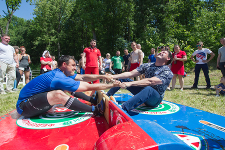 KAZAN, RUSSIA - JUNE 23, 2018: Traditional Tatar festival Sabantuy - Men fighting in national wrestling at summer day outdoors