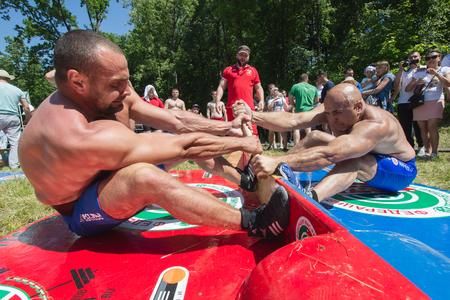 KAZAN, RUSSIA - JUNE 23, 2018: Traditional Tatar festival Sabantuy - Strong men wrestling outdoors at summer day