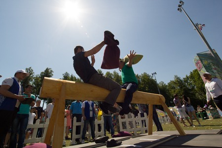 KAZAN, RUSSIA - JUNE 23, 2018: Traditional Tatar festival Sabantuy - Two men on the balance beam fighting with pillows