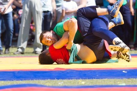 KAZAN, RUSSIA - JUNE 23, 2018: Traditional Tatar festival Sabantuy - Two male wrestlers fighting on tatami in folk kuresh battle