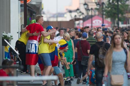KAZAN, RUSSIA - JUNE 22, 2018: FIFA World Cup - Grop of cheerful football fans posing for photogtaph at the Bauman street
