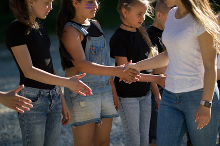 Teenagers teams greeting each other with shake hands outdoors in sunny day Stock Photo