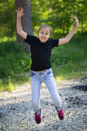Funny teenager girl jumping and having fun in the park at sunny day