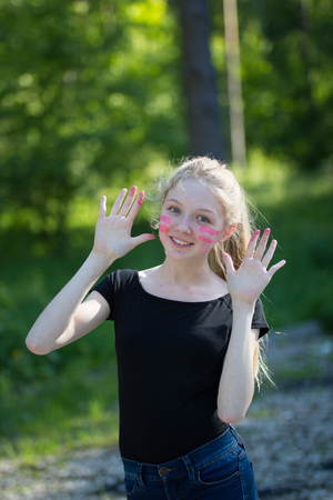 Portrait of funny teen girl smiling with finger paints on her face in summer park Stock Photo