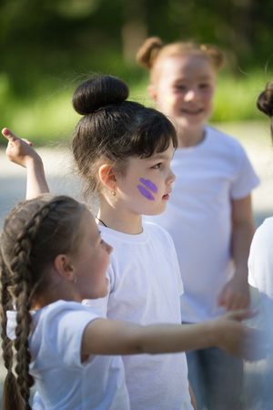 Group of cheerful girls with painted faces having fun in summer park Stock Photo