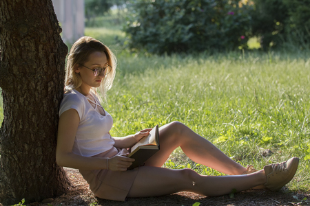 Young attractive woman reading book under the tree in park at su Stock Photo