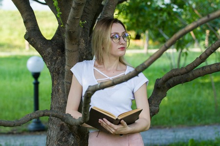 Attractive young woman with a book in the hands in the park leaning on a tree branch