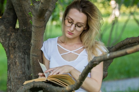 Caucasian young woman reading a book in the park leaning on a tree branch Stock Photo