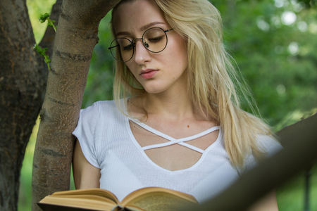 Young woman student reading a book leaning on a tree in the park Stock Photo