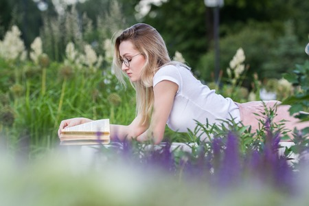 Young beautiful woman reading a book lying on the bench around the grass and flowers at summer day