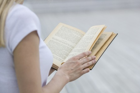 Young female hand holding an old book - reading outdoors