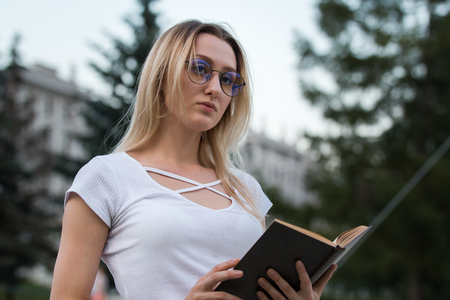 Portrait of a thoughtful girl with a book in her hands outdoors