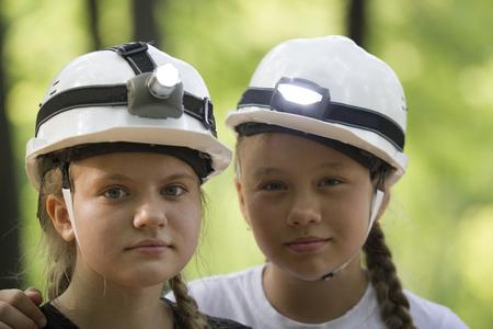 Portrait of cute teen sisters speleologists in helmets in summer Stock Photo