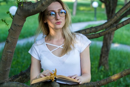 Young woman reading a book sitting in the bushes at summer day