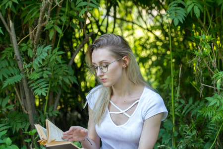 Attractive young woman student reading a book leaning on a tree in the park Stock Photo