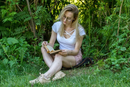 Young attractive woman reading book under the tree in park at sunny day