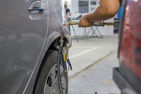 Mechanics hands fix dents on the cars body with a special vacuum device