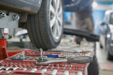 Mechanic tools lie next to the cars wheel on repair 스톡 콘텐츠
