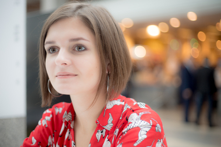 Young women in red shirt looks away on the background of a shopping center