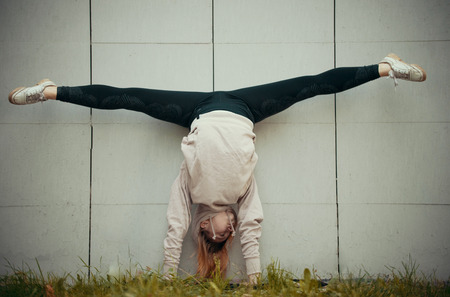 Acrobat girl in a beige hoodie performs the splits while standing on hands on a background of the wall. Wide shot