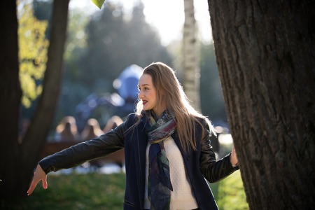 Beautiful girl in a coat next to a tree in autumn sunny park Stock Photo - 109425511
