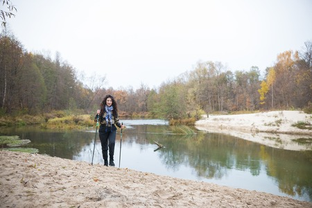 On the banks lake. Curly girl posing in front of lake in forest Archivio Fotografico
