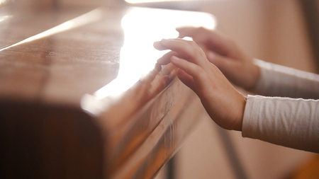 A baby on music lesson. Closed piano Standard-Bild
