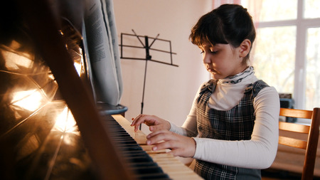 A little girl playing piano on music lesson. Beautiful sunlight