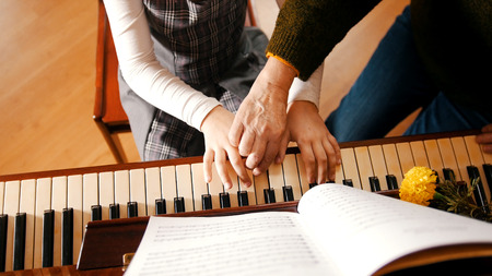 A little girl playing piano on music lesson. A teacher helping her. Hands
