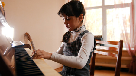 A little girl playing piano on music lesson. Beautiful sunlight. Hands on keys